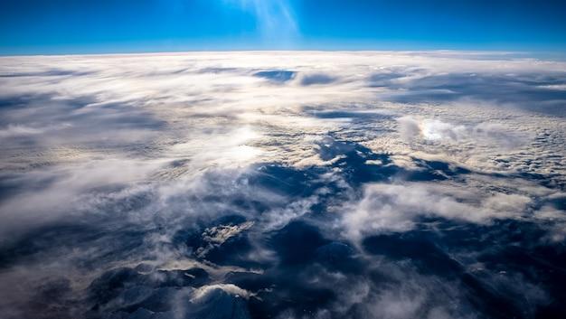 Prachtig uitzicht op de wolken en de bergen onder een heldere hemel geschoten vanuit een vliegtuig