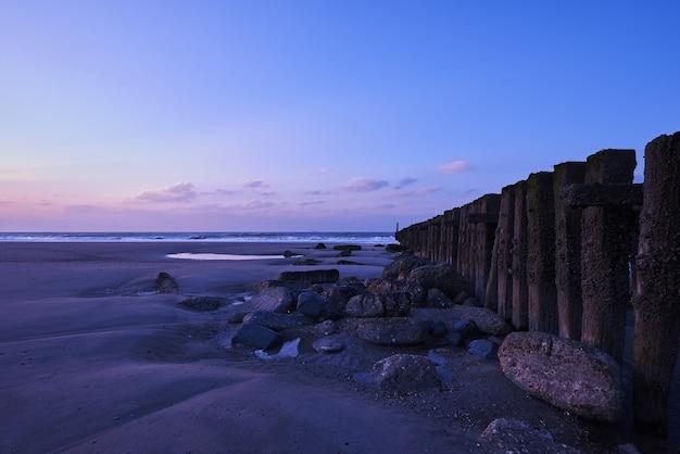 Prachtig uitzicht op de zonsondergang met paarse wolken boven het hek op het strand