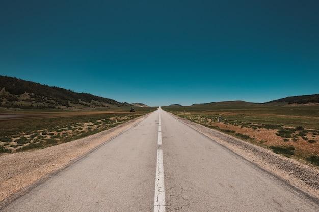 Prachtig uitzicht op een eindeloze weg onder de strakblauwe lucht