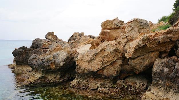 Prachtig uitzicht op een rotsachtig strand met de oceaan en de blauwe lucht