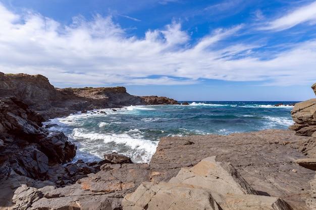 Prachtig uitzicht op een rotsachtige baai met golven op de zee op het eiland menorca, balearen, spanje