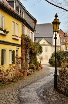 Prachtig uitzicht op een schilderachtig smal steegje met historische traditionele huizen en een geplaveide straat in de oude stad in duitsland met blauwe lucht en wolken in de zomer.