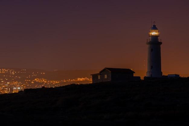 Prachtig uitzicht op een vuurtoren en een huis op een heuvel 's nachts gevangen in cyprus