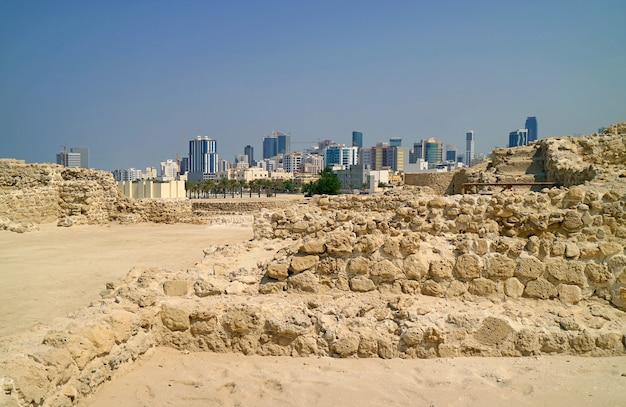 Prachtig uitzicht op het fort van bahrein of de ruïnes van de structuur van qal'at al-bahrain met het moderne stadsbeeld van manama op de achtergrond, bahrein