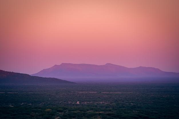 Prachtig uitzicht op het landschap bedekt met groen en bergen op een achtergrond