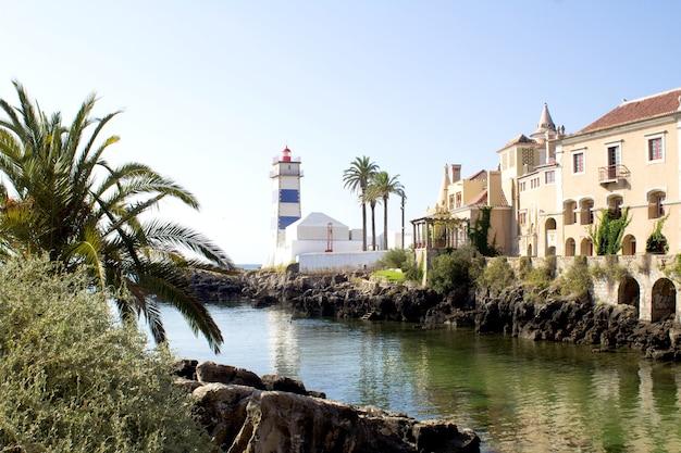 Prachtig uitzicht op het strand, de vuurtoren en de villa op de zonnige dag. cascais. portugal.