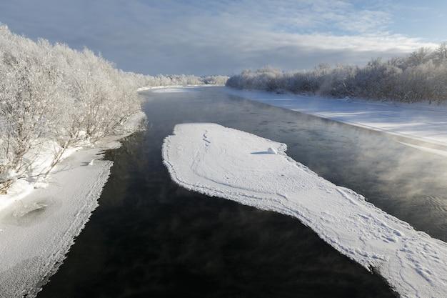 Prachtig uitzicht op het winterlandschap van de rivier met drijvende ijsschotsen op een ijzige dag