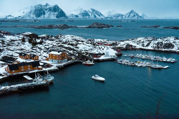 Prachtig uitzicht op houten rode huizen met boten onder de noorse zee. koude en donkere sfeer rondom. besneeuwde rotsbergen op afstand. schoonheid van de lofoten-eilanden