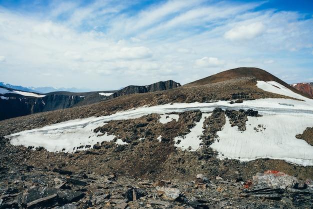 Prachtig uitzicht op kleine gletsjer op steenachtige heuvel onder blauwe hemel met wolken.