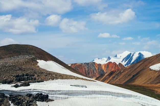 Prachtig uitzicht op kleine gletsjer op steenachtige heuvel onder blauwe hemel