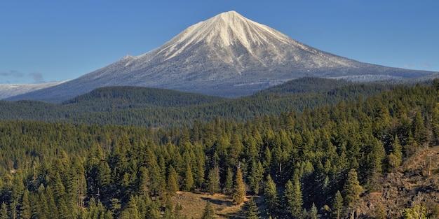 Prachtig uitzicht op mount mcloughlin bedekt met sneeuw over de met bomen bedekte heuvels vastgelegd in oregon