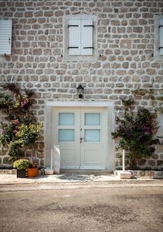 Prachtig uitzicht op oude witte bakstenen muur met ramen en brede deuren