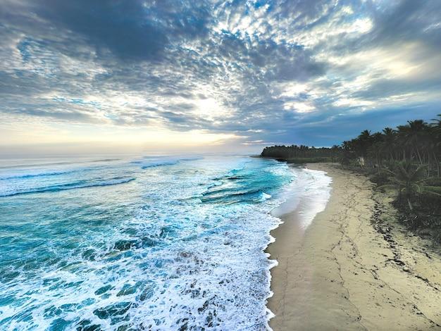 Prachtig uitzicht op schuimende golven die de zandige kust van een tropisch eiland wassen