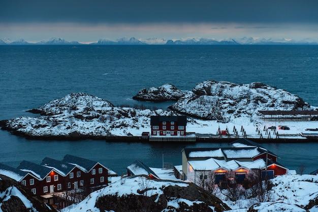 Prachtig uitzicht op traditionele houten huizen gelegen op kleine eilanden onder de koude zee. rotsachtige besneeuwde bergen tijdens bewolkt weer op de achtergrond. noorwegen, lofoten eilanden.