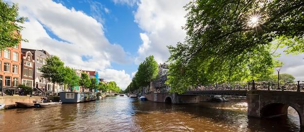 Prachtig uitzicht over de amsterdamse grachten met brug en typisch nederlandse huizen. holland