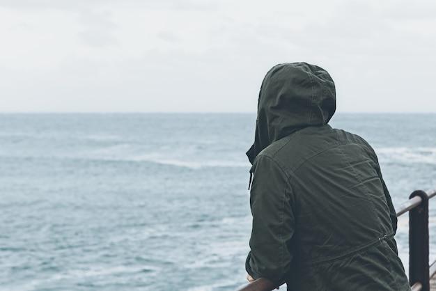 Prachtig uitzicht van een persoon die op het dok staat en naar de oceaan kijkt in het bewolkt weer