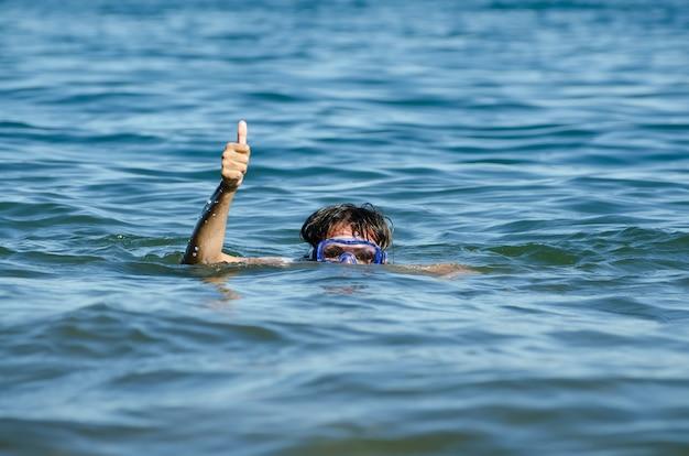 Prachtig uitzicht van een vrouw die in het meer zwemt met alleen haar hoofd en een arm uit het water