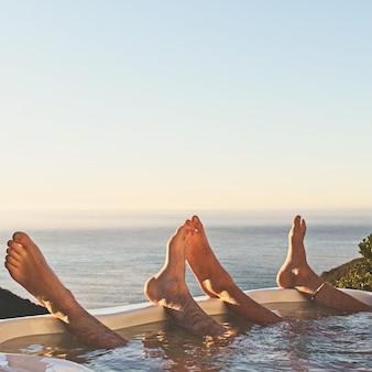 Prachtig uitzicht van twee mensen met hun voeten omhoog bij een zwembad met uitzicht op de oceaan