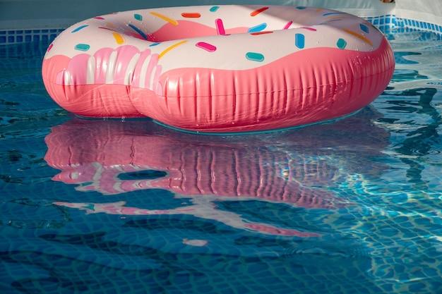 Prachtig verfrissend blauw zwembad met roze opblaasbare donut