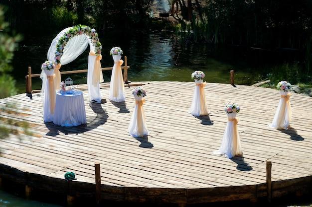 Prachtig versierde huwelijksboog en een kleine tafel, boeketten bloemen voorbereid op ceremonie buitenshuis.