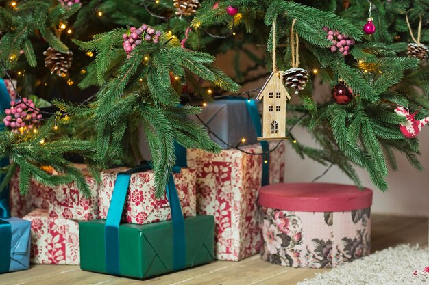 Prachtig versierde kerstboom met veel cadeautjes eronder in nieuwjaars versierd huisinterieur.