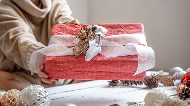 Prachtig versierde kerstcadeau in vrouwelijke handen tegen de muur van decor details close-up.