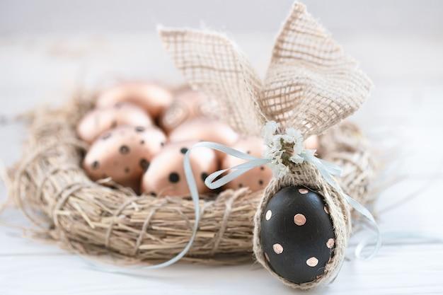 Prachtig versierde paaseieren van gouden kleur met zwarte stippen en een zwart ei met gouden stippen