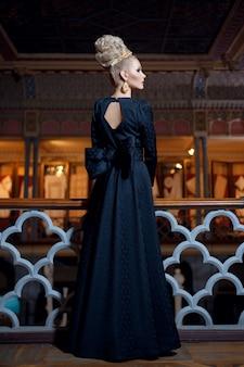 Prachtig vrouwelijk model, gekleed in een lange zwarte jurk met strik aan de achterkant met oorbellen