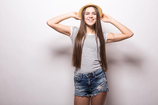 Prachtig vrouwelijk model houdt de hand op een strooien hoed, draagt een witte top met blote schouders, ziet er zelfverzekerd uit, geïsoleerd op een witte muur