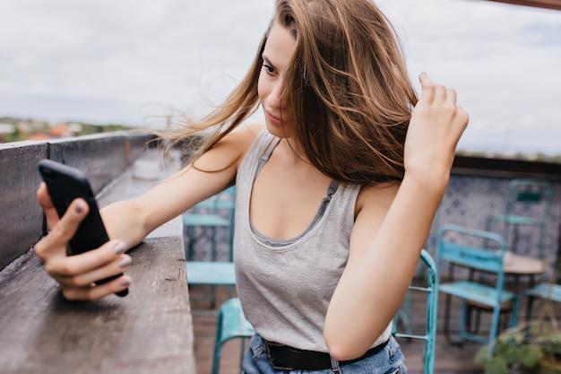 Prachtig vrouwelijk model in casual outfit foto van zichzelf in dak café. buiten foto van prachtige dame spelen met haar haar tijdens het maken van selfie in koude zomerdag.