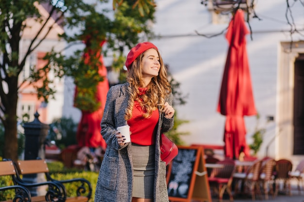 Prachtig vrouwelijk model in grijze kleren lopend onderaan de straat met kopje koffie