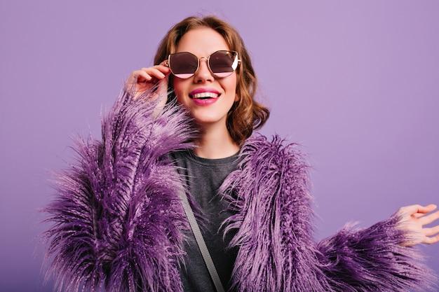 Prachtig vrouwelijk model in verbazingwekkende paarse bontjas op zoek naar camera door middel van zonnebril