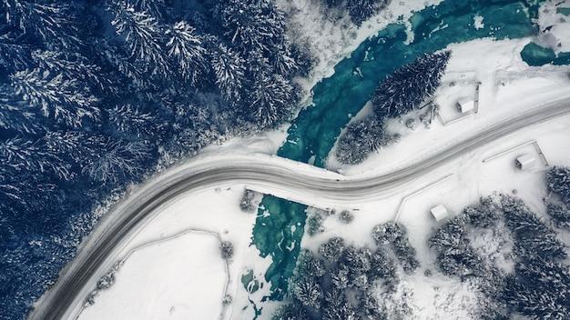 Prachtig winterberglandschap, besneeuwde bergweg met bochten en een bos tot aan de horizon.
