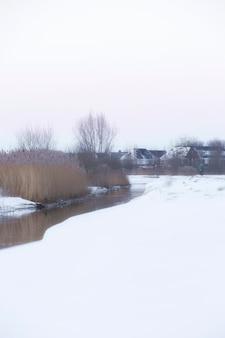Prachtig winterlandschap bij zonsondergang met mist en sneeuw die landbouwgrond en rivier nederland bedekken
