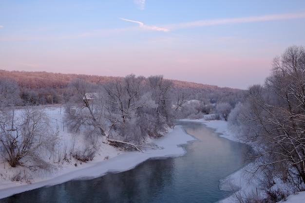 Prachtig winterlandschap met uitzicht op de kronkelende rivier bij zonsopgang en sneeuwbanken