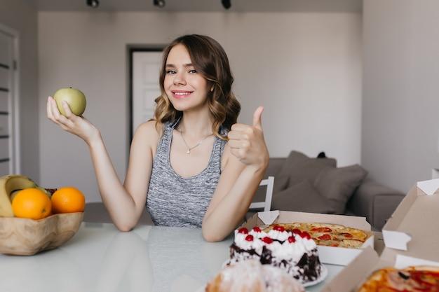 Prachtig wit meisje dat van haar dieet met vers fruit geniet. indoor portret van prachtige vrouw kiest tussen appel en cake.