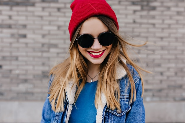 Prachtig wit meisje in stijlvol spijkerjack geïsoleerd op bakstenen muur. met glimlach. buiten foto van elegante lachende vrouw in zwarte zonnebril.