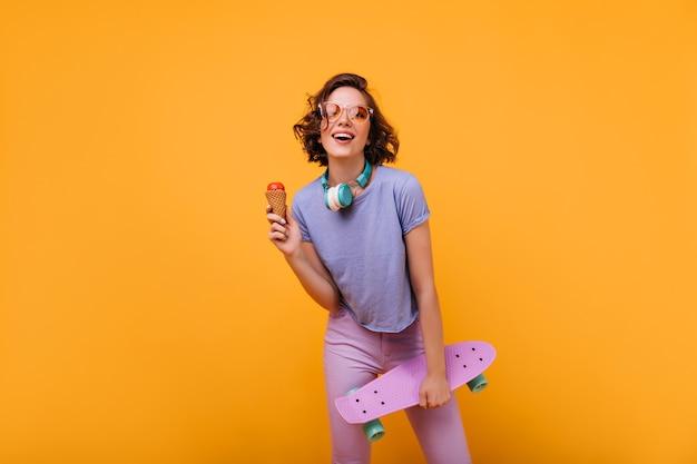 Prachtig wit meisje in vrijetijdskleding poseren in koptelefoon. portret van mooie dame die met skateboard ijs eet.