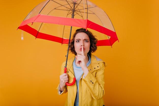 Prachtig wit meisje met kort kapsel aanraken van haar lippen met ernstige gezichtsuitdrukking. binnenportret van knappe vrouw met rode parasol.