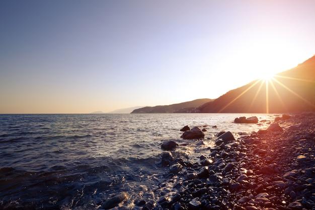 Prachtig zeegezicht dat golven spetterend langs een rotsachtig strand tegen de achtergrond van hoge bergen en heuvels op een warme zonnige zomerochtend. reis concept. advertentie ruimte