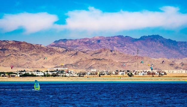 Prachtig zeegezicht en landschap met glorieuze bergen en parachutes