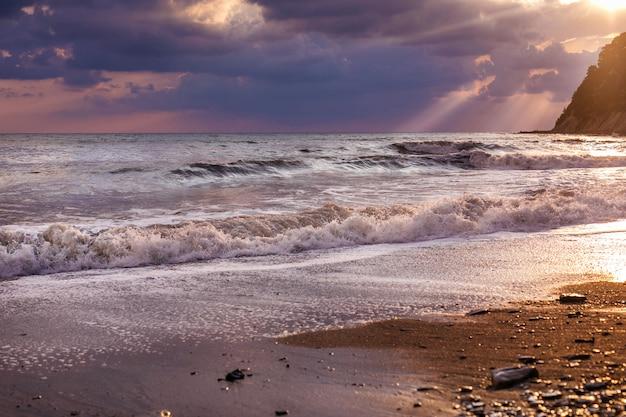 Prachtig zeegezicht met boot op horizon. bewolkte hemel met gouden stralen van de zon, zand kust