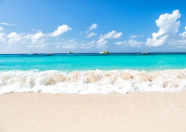 Prachtig zeezicht op de zeekustlijn met schoon golvend surfwater aan de horizon van het zandstrand en bewolkte blauwe lucht op zonnige dag