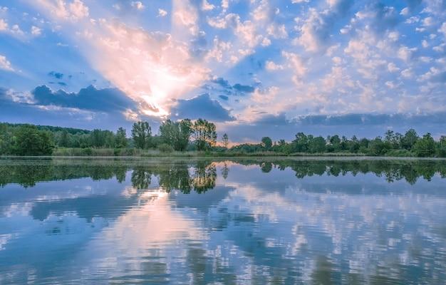 Prachtig zomerlandschap. zonsopgang boven het meer. de zonnestralen schijnen door de wolken.