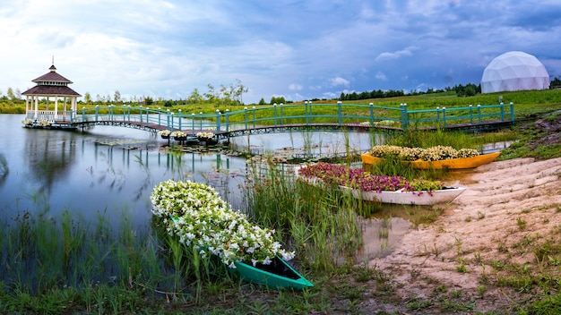 Prachtig zomers landschap en een plek voor meditaties. een houten prieel, een platform en verschillende kleine bootjes vol bloemen aan het meer.