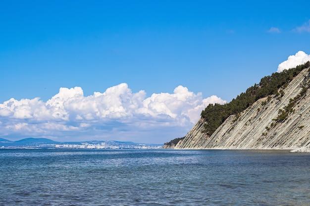 Prachtig zomers landschap, stralend blauwe lucht met wolken, steile kliffen met bomen, stenen wild strand en uitzicht op de stad novorossiysk aan de horizon. rusland, gelendzhik, kust van de zwarte zee