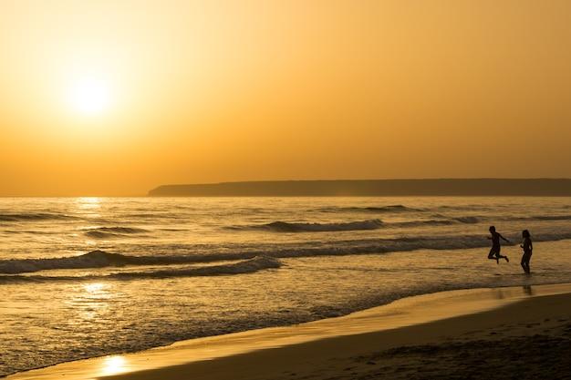Prachtig zonsondergangzeegezicht met mensensilhouet