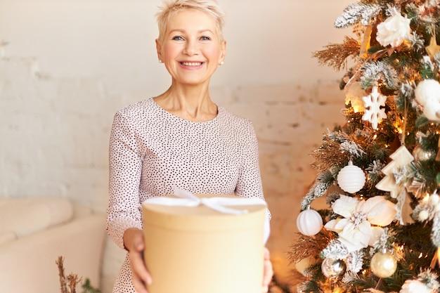 Prachtige 50-jarige europese vrouw in een stijlvolle jurk die je een gelukkig nieuwjaar wenst, een doos met een geschenk met een stralende glimlach voorbijgaat, in feeststemming is. feestdagen, festiviteiten en feesten