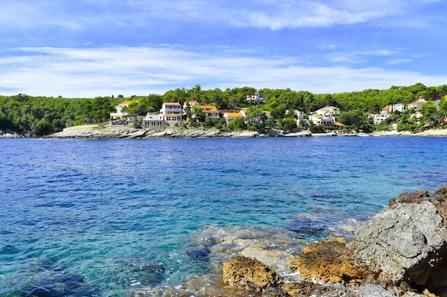 Prachtige adriatische zee in kroatië. blauwe lagune, huizen in groene dennen, rotsachtige kust, mooi