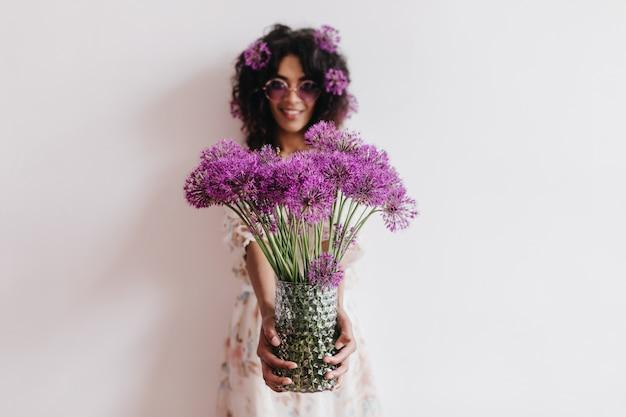Prachtige afrikaanse dame met vaas met paarse bloemen. indoor portret van romantische zwarte jonge vrouw plezier thuis in weekend.